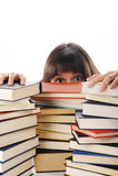 Allievo dietro un grande mucchio dei libri Immagine Stock