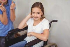 Allievo disabile che sorride alla macchina fotografica con i compagni di classe Fotografie Stock