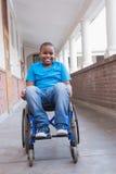 Allievo disabile sveglio che sorride alla macchina fotografica in corridoio Fotografia Stock Libera da Diritti