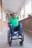 Allievo disabile sveglio che sorride alla macchina fotografica in corridoio Immagine Stock Libera da Diritti