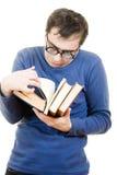 Allievo divertente in vetri con un libro sulla sua testa Fotografia Stock