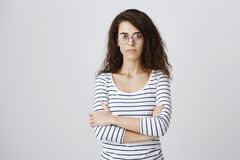 Allievo eccellente che è serio circa gli studi dell'università Bella donna caucasica astuta in vetri con capelli ricci Immagine Stock Libera da Diritti