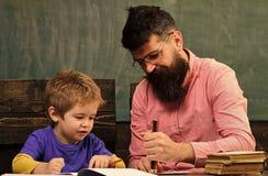 Allievo ed insegnante che assorbono quaderno divertimento del padre che ha figlio insieme Concetto di istruzione prescolastica Fotografia Stock