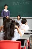 Allievo ed insegnante che si levano in piedi in un banco cinese Fotografia Stock