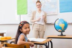 Allievo ed insegnante svegli in aula con il globo Fotografie Stock