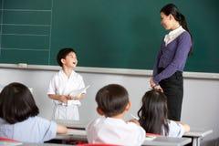 Allievo ed insegnante in un banco cinese Immagine Stock Libera da Diritti