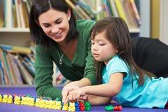 Allievo elementare che conta con l'insegnante In Classroom Immagini Stock