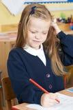 Allievo elementare femminile che soffre dai pidocchi del capo in aula Fotografia Stock