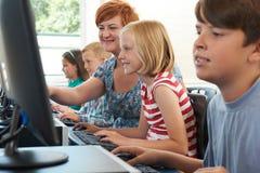Allievo elementare femminile nella classe del computer con l'insegnante Fotografia Stock Libera da Diritti