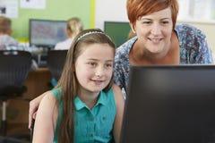 Allievo elementare femminile nella classe del computer con l'insegnante Fotografia Stock