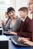 Allievo elementare maschio nella classe del computer con l'insegnante Immagine Stock
