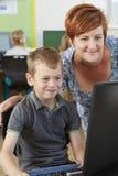 Allievo elementare maschio nella classe del computer con l'insegnante Fotografia Stock
