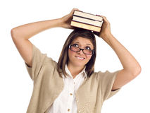 Allievo etnico con i libri sulla sua testa sopra bianco Fotografia Stock