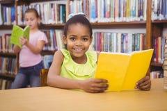 Allievo felice che legge un libro delle biblioteche Fotografia Stock