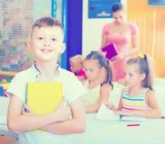 Allievo felice del ragazzo che sta nella classe della scuola elementare Fotografie Stock Libere da Diritti
