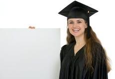 Allievo felice di graduazione che tiene tabellone per le affissioni in bianco Immagine Stock