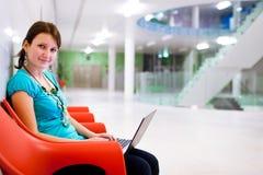 Allievo femminile abbastanza giovane con il computer portatile Fotografia Stock