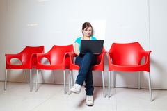 Allievo femminile abbastanza giovane con il computer portatile Immagini Stock