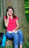 Allievo femminile adorabile - comunicando sul telefono delle cellule Fotografia Stock