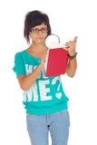 Allievo femminile aggrottante le sopracciglia che osserva nel libro Immagini Stock