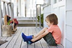 Allievo femminile alla scuola di Montessori che mette su Wellington Boots Fotografie Stock Libere da Diritti