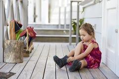 Allievo femminile alla scuola di Montessori che mette su Wellington Boots fotografie stock