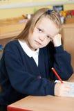 Allievo femminile annoiato della scuola elementare allo scrittorio Fotografia Stock Libera da Diritti