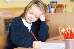 Allievo femminile annoiato della scuola elementare allo scrittorio Immagini Stock Libere da Diritti