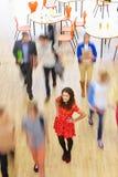 Allievo femminile in aula circondata muovendo gli studenti Fotografia Stock Libera da Diritti