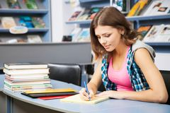 Allievo femminile bello in una libreria Fotografia Stock Libera da Diritti