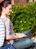 Allievo femminile Charming che per mezzo di un computer portatile BO Fotografia Stock