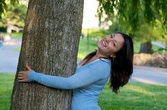 Allievo femminile che abbraccia albero sui campes Fotografia Stock