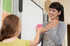 Allievo femminile che dà il regalo di End Of Term dell'insegnante Immagine Stock Libera da Diritti