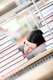 Allievo femminile che dorme allo scrittorio con i mucchi di Fotografie Stock Libere da Diritti