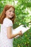 Allievo femminile che fa le note sull'escursione della natura della scuola Immagini Stock Libere da Diritti
