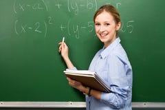 Allievo femminile che fa per la matematica sulla lavagna Immagini Stock