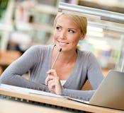 Allievo femminile che impara alla tabella Immagine Stock