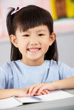 Allievo femminile che lavora allo scrittorio a scuola cinese Immagine Stock Libera da Diritti