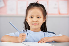 Allievo femminile che lavora allo scrittorio a scuola cinese Fotografia Stock Libera da Diritti