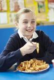 Allievo femminile che mangia la refezione non sana Fotografia Stock