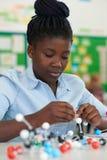 Allievo femminile che per mezzo dei modelli molecolari Kit In Science Lesson Fotografia Stock Libera da Diritti