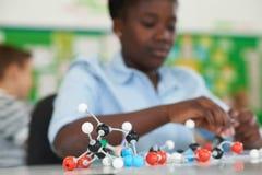 Allievo femminile che per mezzo dei modelli molecolari Kit In Science Lesson Immagine Stock