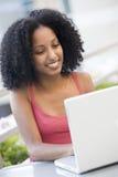 Allievo femminile che per mezzo del computer portatile all'esterno Immagini Stock