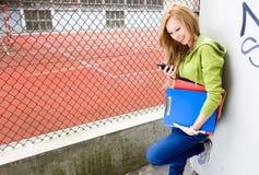 Allievo femminile che per mezzo del telefono mobile Fotografia Stock Libera da Diritti