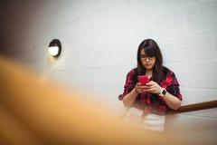 Allievo femminile che per mezzo del telefono mobile Immagine Stock Libera da Diritti