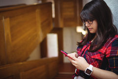 Allievo femminile che per mezzo del telefono mobile Fotografia Stock