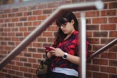 Allievo femminile che per mezzo del telefono mobile Immagini Stock Libere da Diritti