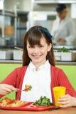 Allievo femminile che si siede alla Tabella nel cibo del self-service di scuola sano Immagine Stock Libera da Diritti