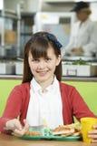 Allievo femminile che si siede alla Tabella nel cibo Unhealt del self-service di scuola Fotografia Stock Libera da Diritti