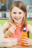Allievo femminile che si siede alla Tabella nel cibo Unhealt del self-service di scuola Immagine Stock